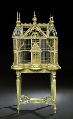 Large Green-Painted and Gilded Wood and Wire Birdcage, first quarter 20th century, in the form of a gabled and turreted mansion with turned giltwood roof finials, presented on a conforming matching table in the Louis XVI manner of Adam Weisweiler