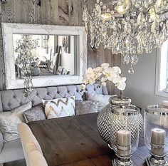 Grey rustic glam. Great use of a mirror to reflect the light from the chandelier - adding extra sparkle!