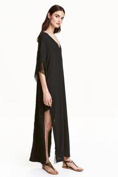 Caftan à franges: Long caftan en tissu crêpé. Modèle avec encolure en V, couture d'épaule descendue et manches courtes. Franges sur les côtés et fentes à la base. Doublé.