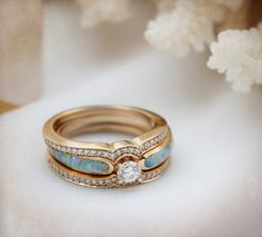 Unique rose gold opal engagement ring with two diamond bands. The red flecks in the opal match the rose gold beautifully! | The Alchemy Bench #bridaltransformed