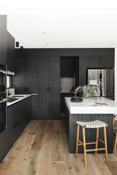 Dark joinery and pops of terrazzo steal the show in this modern home makeover. Terrazzo splashback in kitchen, window splashback in kitchen, black and white kitchen, modern kitchen, built in ovens in kitchen, hidden laundry in kitchen cupboard