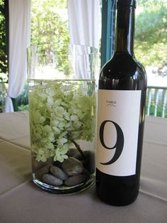 SIMPLE centerpieces with river rocks and simple white flowers. Table numbers in this photo not the ones we'd go with.