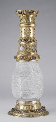 """Vase de cristal """"d'Aliénor''   Provient du trésor de l'abbaye de Saint-Denis  Cristal : Iran ?, VIe - VIIe siècle ?  Monture : Saint-Denis, avant 1147 ; XIIIe et XIVe siècles  Cristal de roche, argent niellé et doré, pierres pécieuses, perles, émaux champlevés sur argent    Inscription :  (ce vase, Aliénor, son épouse, l'a donné au roi Louis, Mitadolus à son aïeul, le roi à moi, Suger, qui l'ai offert aux saints)."""