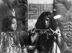 Two Maori girls dressed in korowai (tag cloaks), with tiki around their necks and feathers in their hair. One is playing whai (string games). Photograph taken by the New Zealand Government Tourist Department circa Nz History, History Facts, Maori Songs, Polynesian People, Maori People, Maori Designs, National Symbols, Maori Art, Memorial Museum