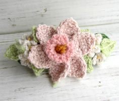 This hair barrette is made on a grass green cotton and wool base with flowers in cashmere in the colors of light pink, medium pink, and off white with celery green leaves. Has a bit of celery green mohair.