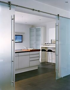frosted glass barn doors can be closed to separate spaces while letting light through