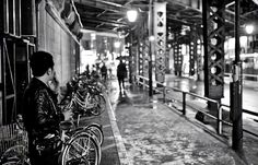 Enjoying a smoke and a hot can of coffee on a rainy night under the train bridge in Tokyo's Kanda station.