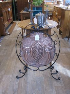 Unusual shaped round beaten copper panel on wrought iron frame