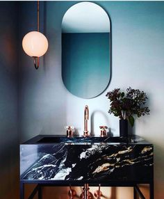 Love this moody powder room and how the brass and marble play off each other. #Bathroom #Mirror