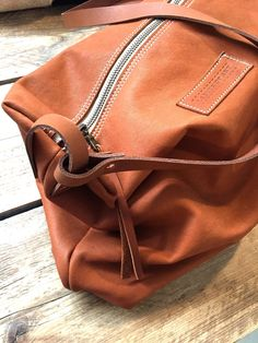 Small Duffle Bag, made from Cognac colored Eco Leather. Smooth leather with natural marks. A Zippered Crossbody with adjustable Leather Strap, that fit an ipad and your daily essentials. Inside zip...
