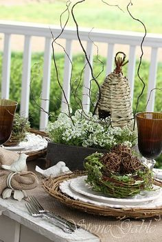 Love all the natural mix for this spring tablescape...... wicker chargers, bird nest , old wooden box container of white fresh flowers, moss, bird accent pieces!