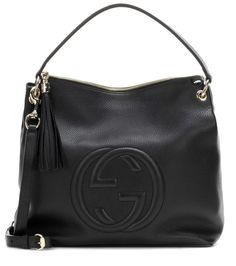 Gucci - Soho leather shoulder bag - With the label's logo stitched on the front with an embossed effect, Gucci's Soho shoulder bag is synonymous with luxury. The roomy black leather piece is perfect for toting around all your essentials on busy days or long-haul flights. Note the pale gold-tone hardware and exaggerated tassel adding a glamorous finish. seen @ www.mytheresa.com