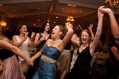 Moving in a circle with hands linked, a bridesmaid in a cobalt blue satin gown with a tan sash and pearls sings along with fellow wedding guests and premier wedding band City Heat at the Oakmont Country Club, Pittsburgh. The newlyweds and their guests danced all night long in the classic venue, celebrating their new marriage. http://www.cityheat.us/weddings.html
