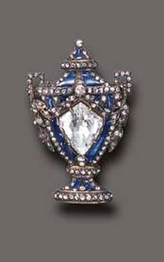 A RARE GEORGIAN DIAMOND AND ENAMEL BROOCH  Designed as a blue enamel urn, centering upon a modified briolette-cut diamond, enhanced by rose-cut diamond trim, mounted in silver and gold, circa 1820 Numbered 32