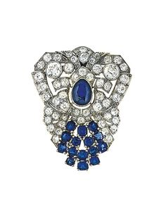 An Art Deco sapphire and diamond brooch. Of old brilliant-cut diamond-set openwork stylised shield-shape design with central pear-shaped sapphire collet and cushion-shaped sapphire cluster flared terminal,  circa 1930