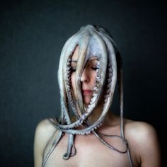 [French photographer Emmanuelle Brisson created a series of portraits entitled 'Can't get it out of my head'. Unlike other portraits she focuses not on the face itself but on a woman wearing pretty questionable headgears. From an octopus suction-cupped to her scalp to Christmas lights tightly wound around her face, fantasies, fears and thoughts seem to be growing out of this womans head, finding expression in various objects.]