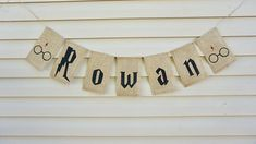 Custom Name Banner with Harry Potter font. The banner shown in pictures is 100% handmade. Its made of 7 hand painted pieces of burlap. Each flag measures approximately 8 x 5 1/4. There is about 26 of twine on each side for hanging. Letters spelling ROWAN (in this case) with Harry
