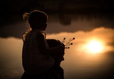 Fatherly love. Silhouette photography by Darah Soria Photography in Wichita Falls, TX.  Taken at 35mm, f/2.0 and using the lake as backlighting.