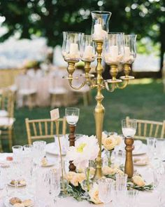 Round tables were scattered throughout the garden and topped with blush pink linens and gold accents. Individual vases of flowers and antique candelabras were used as centerpieces to give the tables an elegant, warm feel.