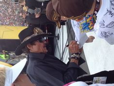 The King Richard Petty autographs the shirts of two young fans at driver introductions for the Sprint Showdown.