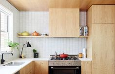 oak cabinets lend the perfect hint of contrast against a Japanese Inax tile installation.