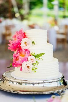 Three tiered buttercream wedding cake with fuchsia peonies and pale pink roses on a stunning silver cake stand.