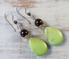 Green from Down Under Dangling lemon chrysoprase briolettes with large garnet beads, gold filled wavy discs and fancy sterling silver ear wires. Most lemon chrysoprase is mined in Australia. Lemon chrysoprase is said to enable us to manifest what we truly desire in our heart.
