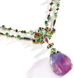 Alternate view: Art Nouveau necklace by Louis Comfort Tiffany of Tiffany & Co., circa 1914-1927. It features a double-chain of small fancy-shaped links applied with champlevé enamel in shades of blue, green and plum, spaced at intervals by cabochon emeralds. The center of the chain is decorated with a large floral link enameled in blue and green and set with cabochon sapphires, rubies, and an emerald. The center of the chain supporting an unusual blue and plum colored sapphire drop. Via…