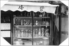 1965 Korean Street Life ~ Snake Store in Seoul    Downtown Seoul, South Korea, at a store in 1965 where you could buy snakes - they had living snakes inside the store. The store even sold poisonous snakes. I believe the snakes were sold for medicinal purposes; but I bought a couple to keep as pets (see my UN Village photo set for examples)!    //    Ironically, it says 'candy' on the top...