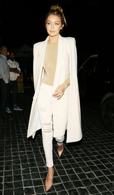 Gigi Hadid looks sleek in a nude top, long white coat, distressed skinny jeans, and nude heels