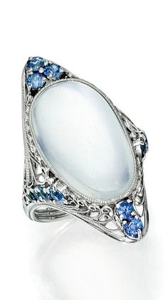 Louis Comfort Tiffany for Tiffany & Co. - An Antique Moonstone and Sapphire Ring, Circa 1915. Set with a moonstone cabochon, within a decorative scrollwork mounting accented with round sapphires, signed Tiffany & Co.
