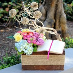 There's something romantic about vintage books. And when you pair them with flowers in a timeworn crate, they make a unique, personal gift that would make Jane Austen proud. This arrangement's literary theme even extends to the pom pom rosettes made from book pages. A beautiful centerpiece or gift for Valentine's Day, Mother's Day, weddings... or...