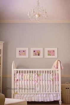 A feminine girl nursery with blue gray walls and a pretty pink ceiling.