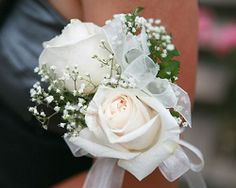 White Rose Corsage for mothers and grandmothers. 2 white roses and baby's breath (similar to groomsmen corsage) - no ribbon. 4 total