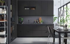 A kitchen with anthracite units, and dark gray walls and dining table.