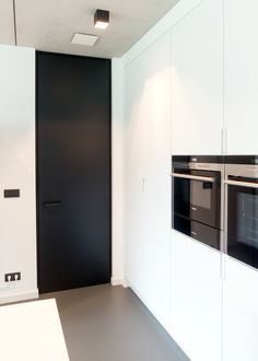 Modern black interior door from floor to ceiling in a all white kitchen.