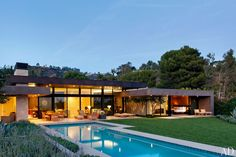 The house, which is tucked into a hillside to maximize space for the terraces, lawn, and glass-tiled pool, is marked by deep roof overhangs that provide shade and extend the architecture into the outdoors.