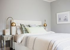 Homepolish Interior Design | A quiet and relaxed bedroom was achieved by painting the walls a light gray and choosing a slightly colder - al...