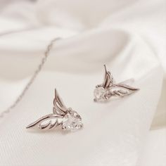 Give your outlook an infinitely versatile touch with these twinkling angel wings earrings. The earring is made up of highest quality sterling silver .925 into a classic and recognizable shape. The earrings are adorned with sparkling circular zircons and fasten with strong fittings that are only for pierced ears only. Mix match with similar angel wings jewelry for a perfect outlook.