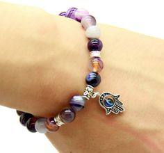 One our most popular items, and for a good reason its gorgeous! Statement fashion bracelet, with purple agate beads and a Hamsa charm for protection. The cord stretches to accommodate different size w