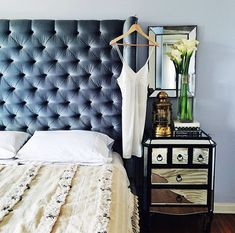 Make your room look more expensive with a blue velvet tufted headboard and a mirrored bedside table