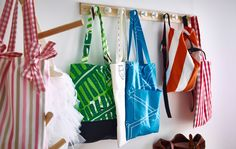 Different colored and different patterned tote bags hanging from wall hooks and a hat rack.