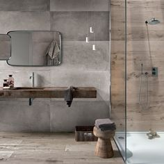 rustic small bathroom with wood color ceramic walls white flooring in the shower area, grey stones wall and wooden flooring in the brown sink area with mirror, javanese traditional wooden chair