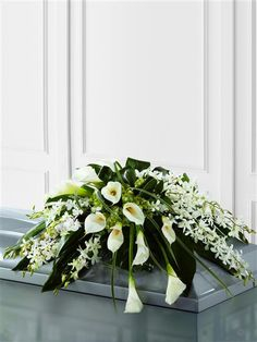 Callay Lily and Orchid Casket Spray. White Dendrobium orchids, white calla Lily, green hydrangea and a variety of lush green leaves are expertly arranged to create a very graceful casket spray.
