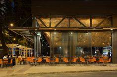 Sob a pérgola com tecido na cobertura, mesas na calçada dão aspecto informal ao espaço exterior do Olga Nur
