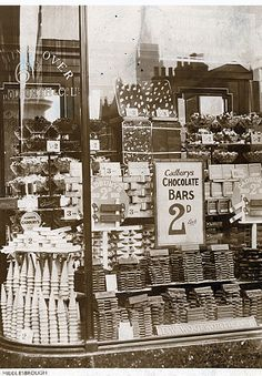 Weigh out sweets and miniature 3oz (85g) chocolate bars from Cadbury in the windows of Woolworths Middlesborough store in the early 1930s.