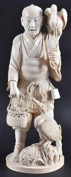 A FINE 19TH CENTURY JAPANESE MEIJI PERIOD TOKYO SCHOOL OKIMONO the fisherman modelled standing holding a basket with his catch, with two cormorants on his shoulder and by his side. Signed. Good condition. 12.5ins high.