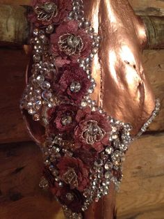 Custom copper cow skull with hand beaded lace and rhinestones .