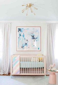 I love this large abstract painting over the crib of this girl nursery! The ceiling light is really stylish for a kids room. Plus, the light pink color creates a little vintage feel in this girly room design. Follow us for more baby room idea! Visit mysleepymonkey.com to catch the latest trends!