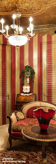 A bold touch of color using the red, but softened by the gold. Mixture of stripes (walls) contrasting nicely with the patterned rug and sofa.